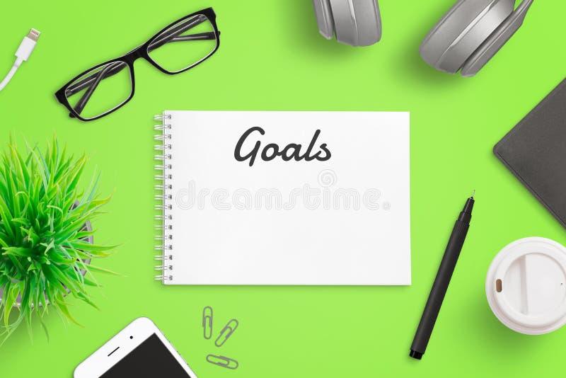 Inscription des buts sur le concept de page de bloc-notes Bureau vert avec le téléphone intelligent, verres, dossier, café, usine image libre de droits