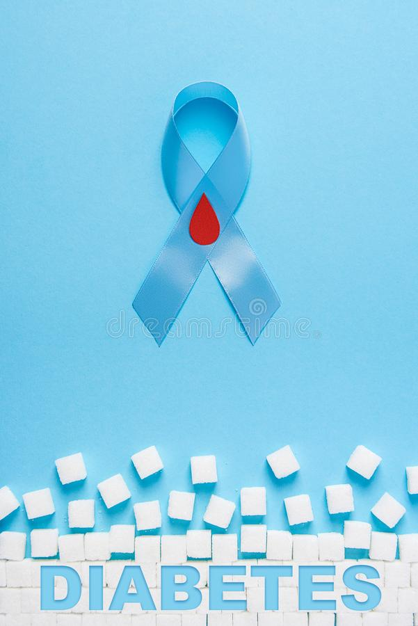 Inscription diabetes blue ribbon awareness with red blood drop and ruined wall made of sugar cubes on a blue background royalty free illustration