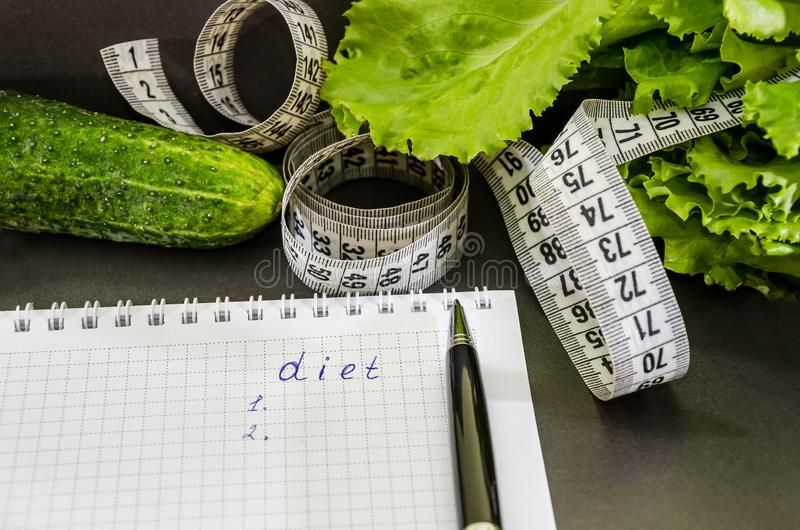 The inscription `diet` on a notebook, dollars, coins and vegetables on the table royalty free stock photos
