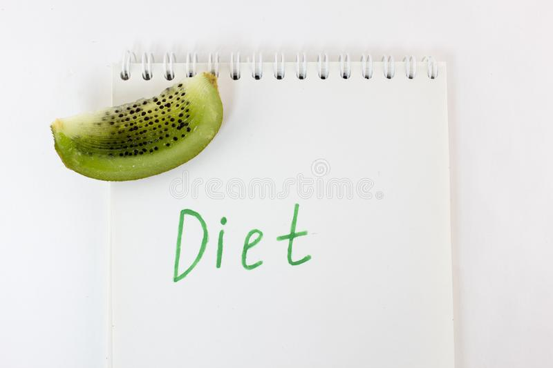 Inscription diets on a notepad and a slice of kiwi on a white background dieting. Inscription diets on a notepad and a slice of kiwi on a white background stock photography