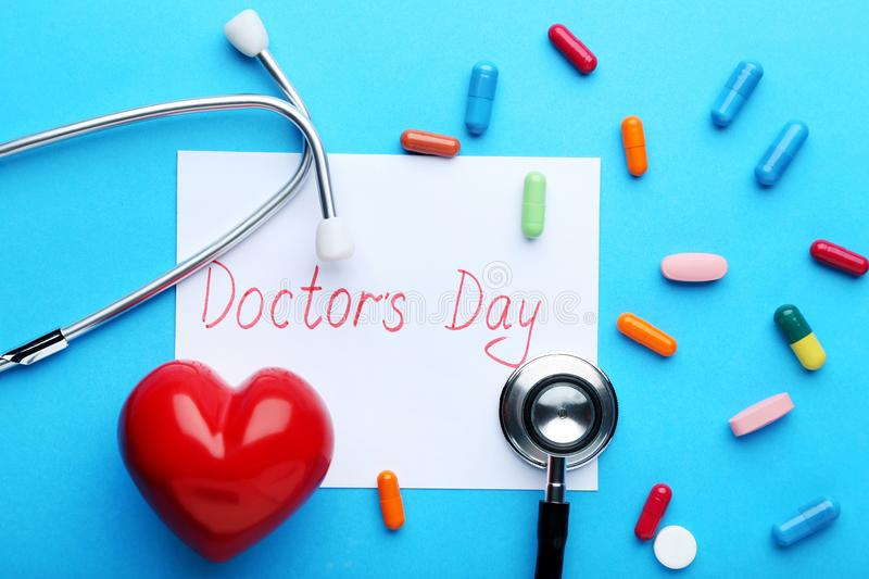 Inscription Doctors Day with pills, stethoscope royalty free stock photo