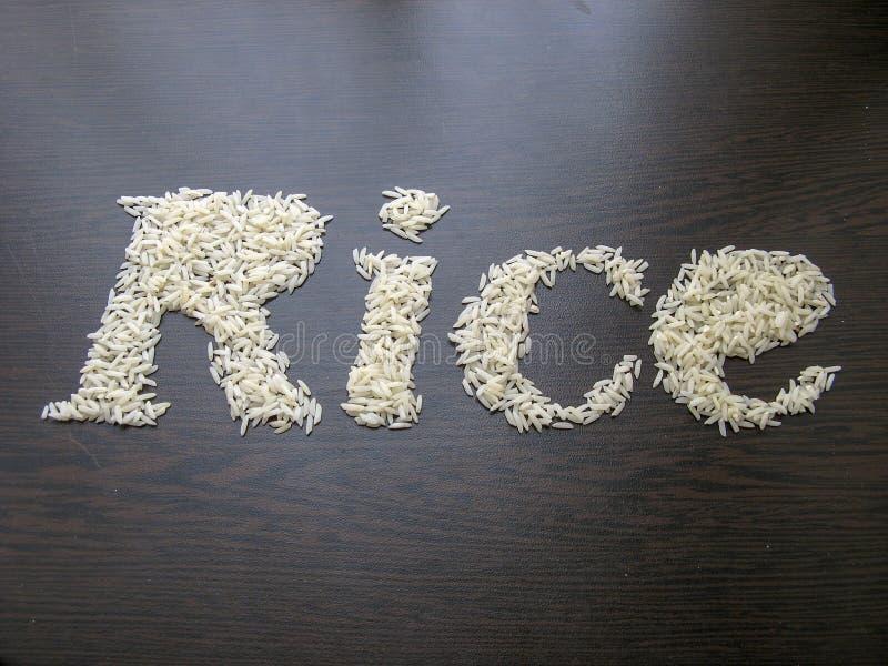 Inscription du riz de mot avec des graines de riz sur une table avec le fond en bois brun image stock