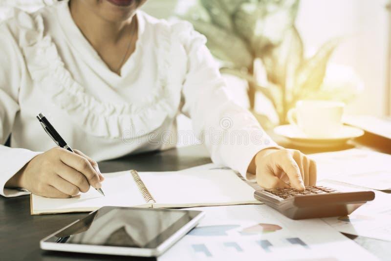 Inscription et mémoire de femmes d'affaires sur le carnet et la presse sur le calcul photo stock