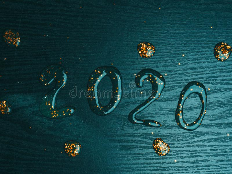2020 inscription from festive gold slime. On wooden background royalty free stock photo