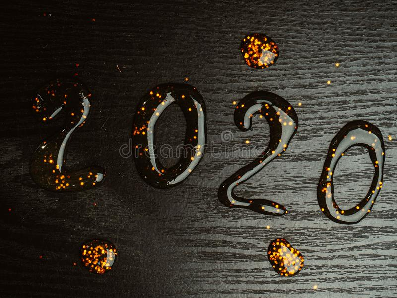 2020 inscription from festive gold slime. On wooden background stock photos