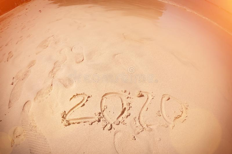 Inscription with a finger on the sand. Figures happy new year 2020. Fisheye lens royalty free stock photos