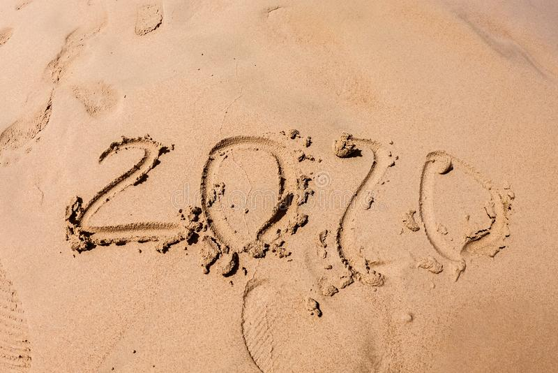 Inscription with a finger on the sand. Figures happy new year 2020.  With traces of people in the sand royalty free stock images