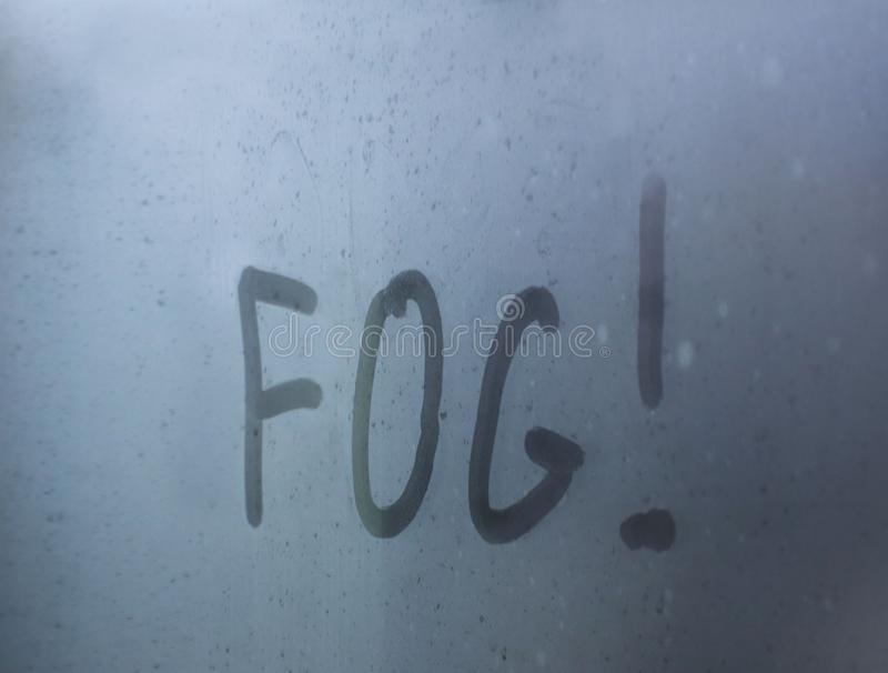 The inscription - `fog` written by a finger on a misted glass with mkrymi drops. Warning motorists about the dangers on the road stock photo