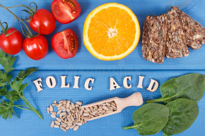 Inscription folic acid with healthy nutritious food as source minerals, vitamin B9 and dietary fiber. Inscription folic acid with nutritious food as source royalty free stock photo