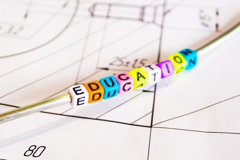 The inscription - the formation of multicolored letters on the background of technical drawings.  stock photo