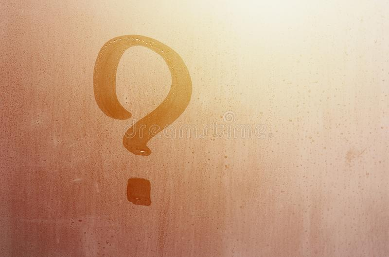 The inscription on glass, question mark concept. Question sign is painted on the surface of misted and wet window royalty free stock images
