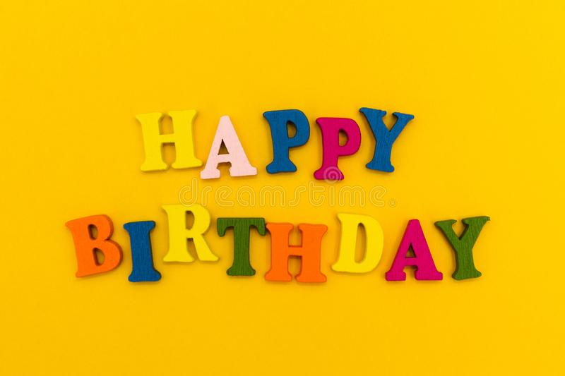 The inscription `Happy Birthday` in colorful letters on a yellow background stock photos