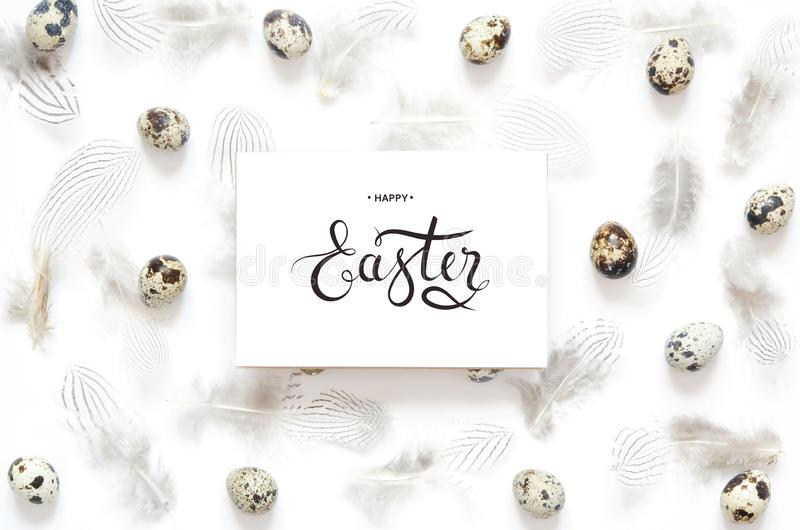 Inscription Happy Easter. Pattern with quail eggs and feathering on white background stock photography