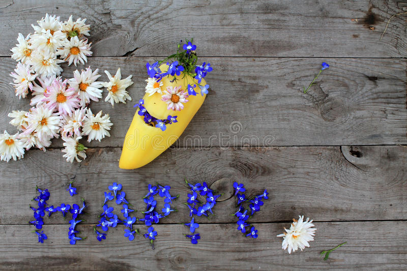 Inscription `Happy` from flowers on wooden background with pepper in form of emoticon, with copy space. Optimistic inscription `Happy` from flowers on old royalty free stock photos