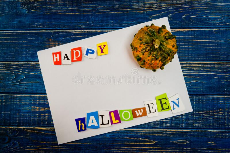 Inscription `Happy Halloween` with empty copy space and pumpkin on wooden blue table. Halloween Background stock photography