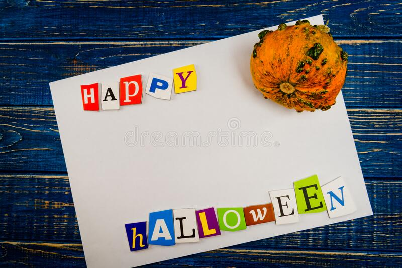 Inscription `Happy Halloween` with empty copy space and pumpkin on wooden blue table. Halloween Background stock images