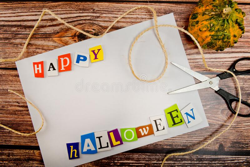 Inscription `Happy Halloween` with empty copy space on wooden table with pumpkin, scissors and lashing. Halloween Background. Top view stock photos
