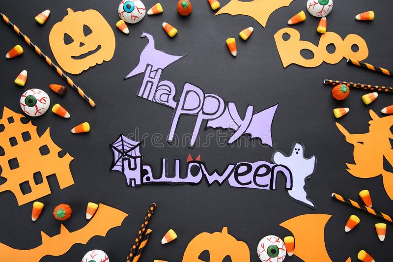 Inscription Happy Halloween. With candies and paper decorations on black background stock photo