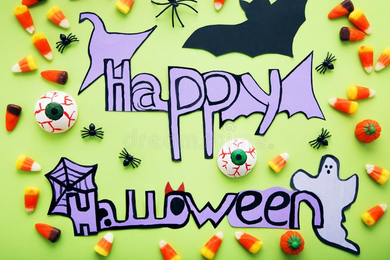 Inscription Happy Halloween. With candies and paper decorations on green background stock photography