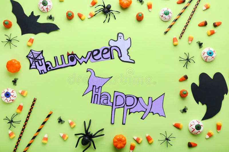 Inscription Happy Halloween. With candies and paper decorations on green background royalty free stock photo