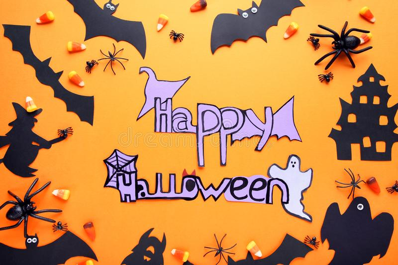 Inscription Happy Halloween. With candies and paper decorations on orange background stock images
