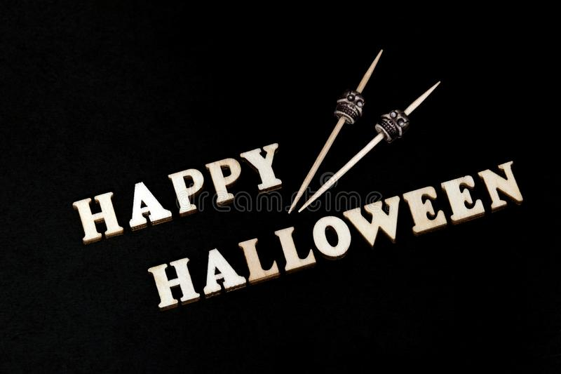 The inscription HAPPY HALLOWEEN made of wooden letters on a black background and two skulls on sticks. Decoration on the day of al stock images