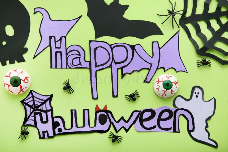 Inscription Happy Halloween. With paper decorations on green background stock photos