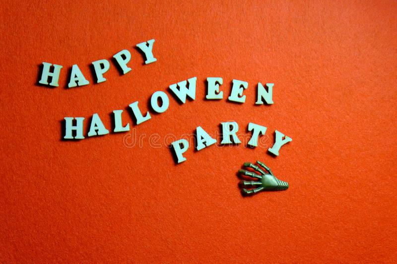Inscription HAPPY HALLOWEEN PARTY made of wooden letters on an orange background. The claw of the monster lies next to the words i. Inscription HAPPY HALLOWEEN stock photo