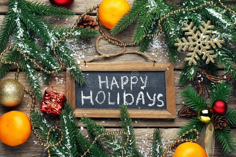 Inscription Happy Holiday. On wooden frame with fir-tree branches and mandarins stock images