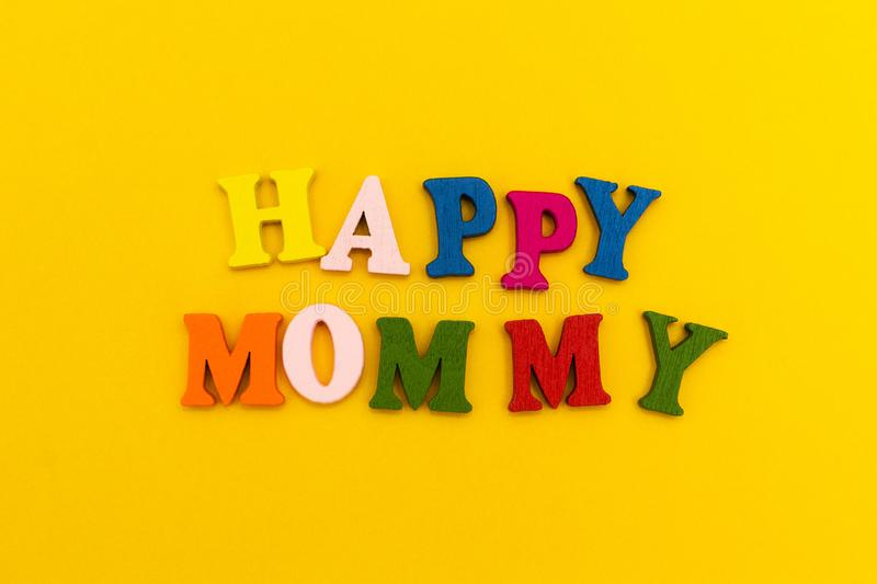 The inscription `Happy Mommy` in colorful letters on a yellow background stock images