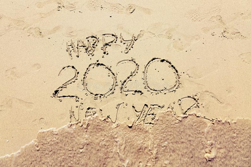Inscription happy new 2020 on beach sand, wave covering text. New Year 2020 is coming concept royalty free stock photo