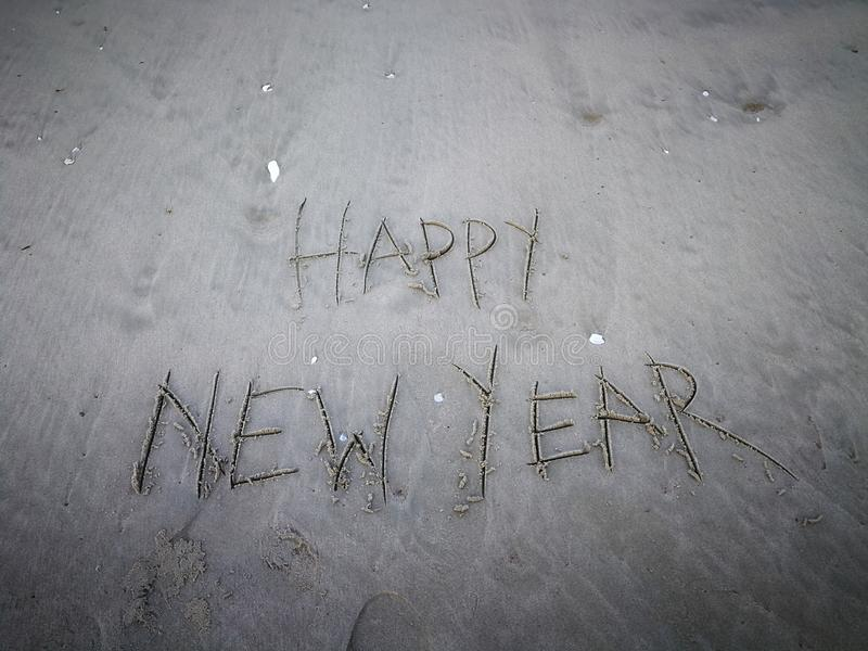 Inscription happy new year and human footprint in the sand on the beach. stock photos