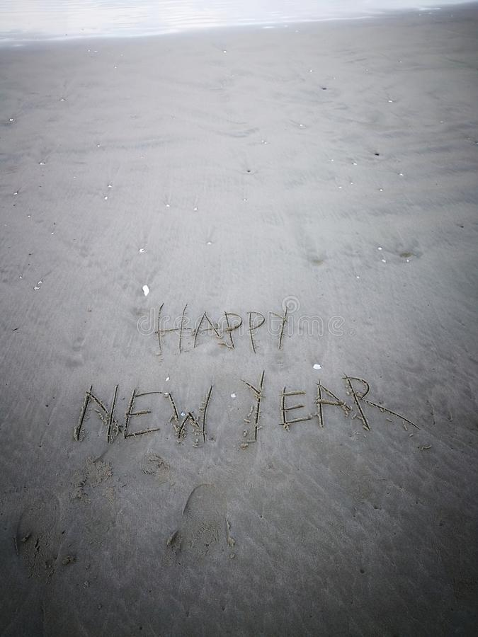 Inscription happy new year and human footprint in the sand on the beach. stock photo