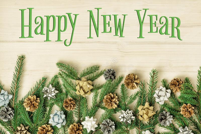 The inscription Happy New Year on a light wooden background. Beautiful Christmas composition of fir branches decorated royalty free stock images