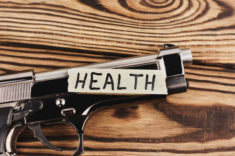 Inscription HEALTH on torn paper and glossy pistol stock photo