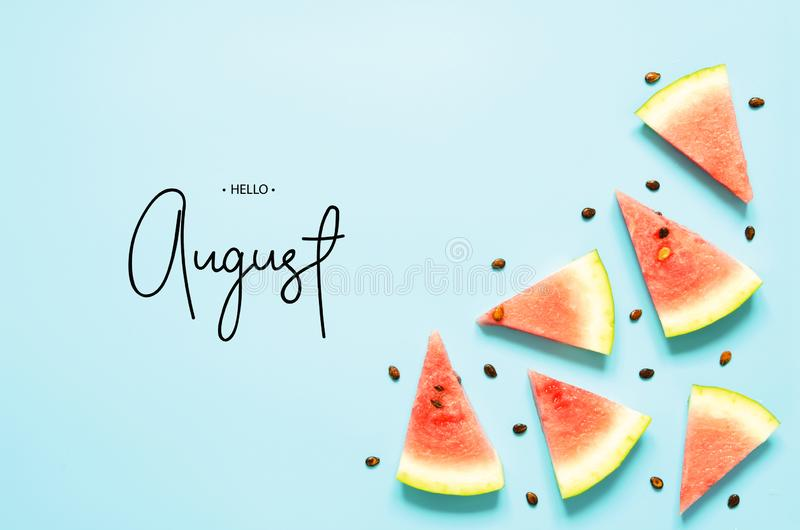 Inscription Hello August. Fresh red watermelon slice Isolated light blue background. Top view, Flat lay. stock image
