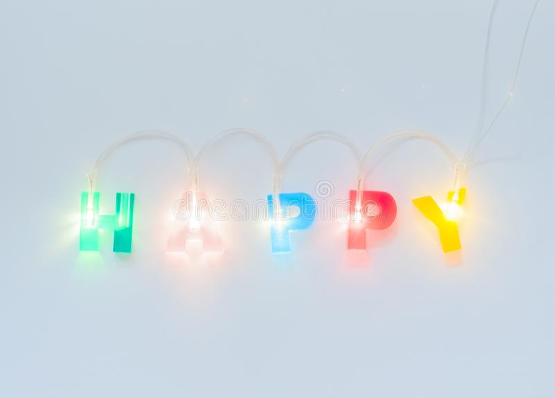 Inscription heureuse Lettres rougeoyantes multicolores sur le fond mat blanc Lettrage volumétrique mené photos stock