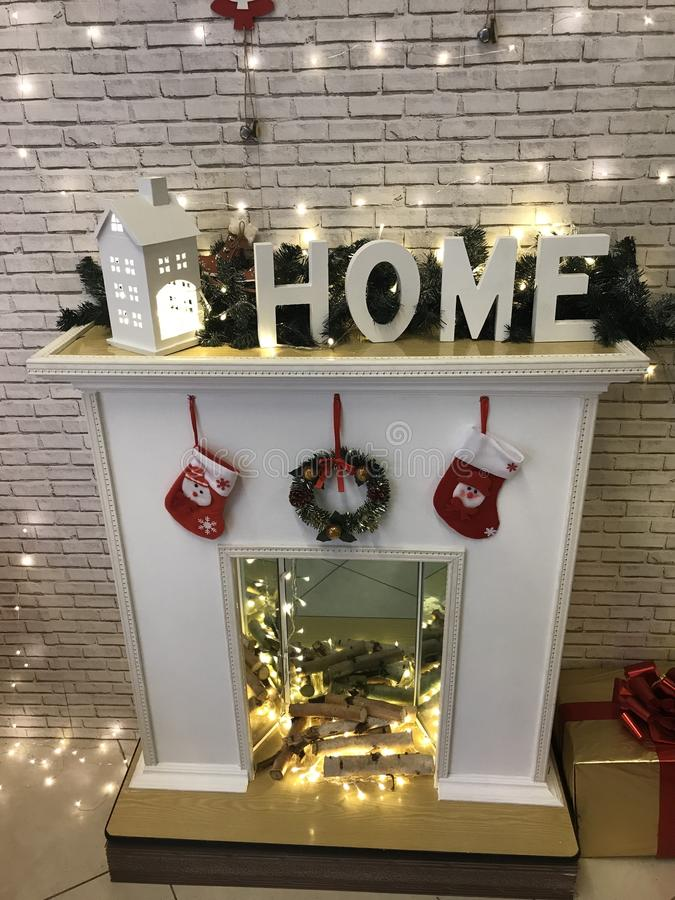 The inscription `home` from large white plastic decorative letters, a small toy glowing house stand on an artificial fireplace a stock photography