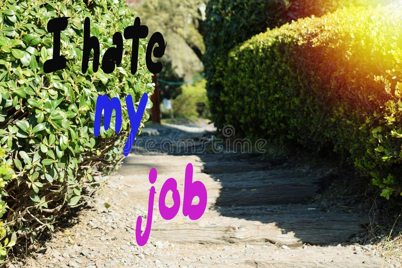 The inscription, I hate my job, against the background of the path in the park on a sunny summer day.  royalty free stock images
