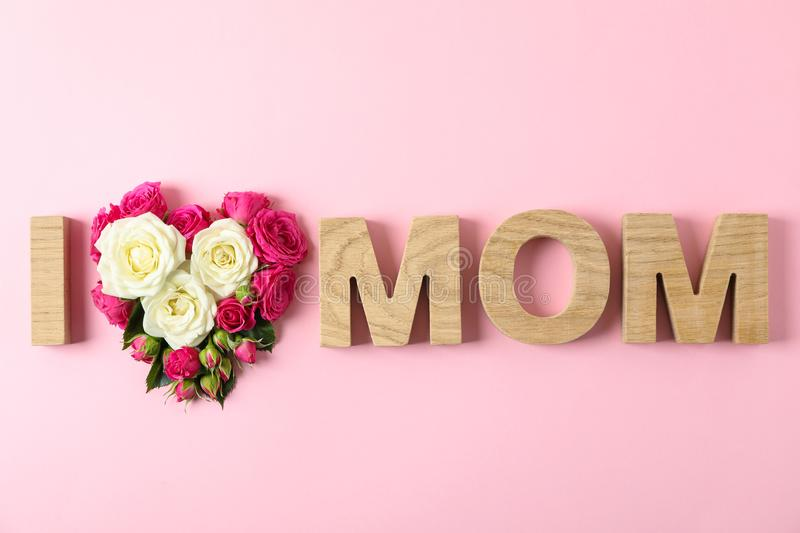 Inscription I Love Mom with roses in shape of heart on color background royalty free stock photos