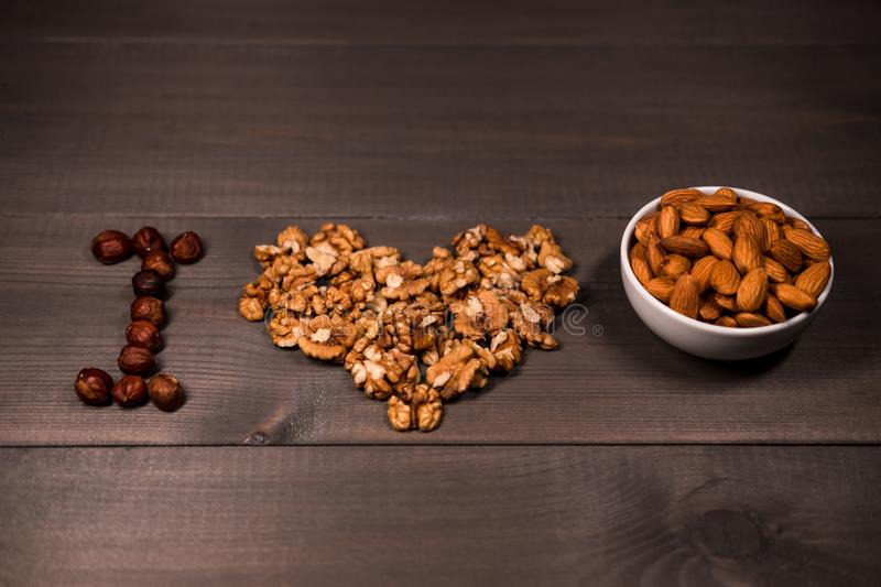 Inscription I love nuts, from nuts, walnuts, almonds and hazelnuts and one white cups with nuts. On brown wooden background stock image