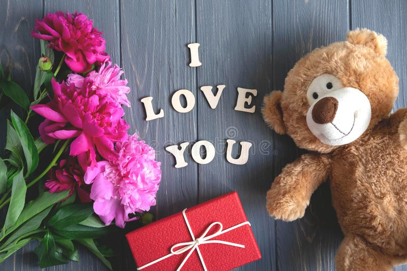 Inscription I love you. A bouquet of peonies on a wooden background with a gift, a toy bear. Pink and maroon peonies on a dark royalty free stock images