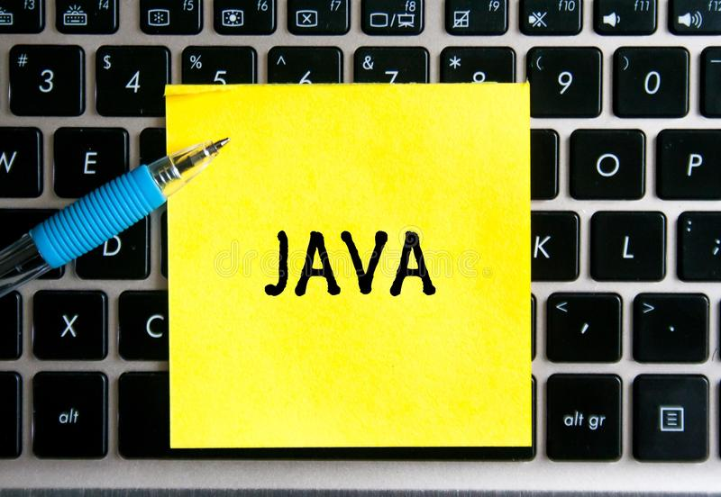 The inscription `JAVA` on a yellow sheet of sticker paper stock photography