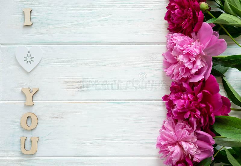 Inscription je t'aime Pivoines de rose et de Bourgogne sur un fond en bois avec l'espace pour la rédaction publicitaire Vue pour  photo stock
