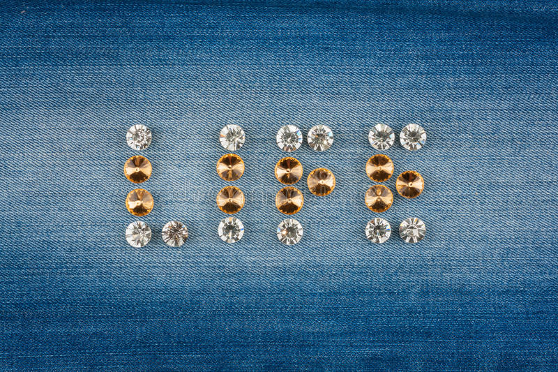 Inscription LIFE made of rhinestones, on jeans. Background royalty free stock photography
