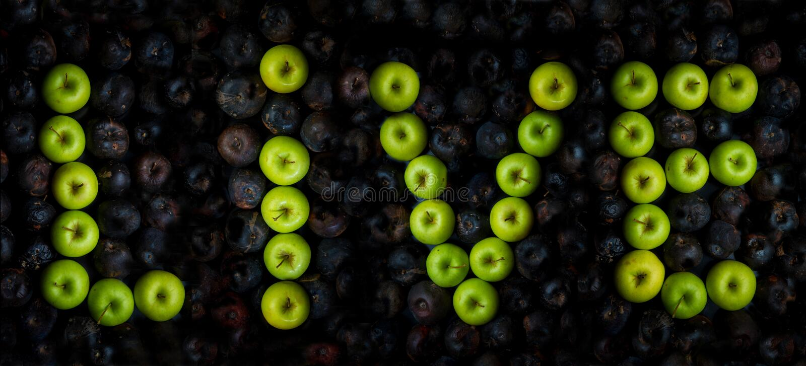 the inscription LIVE with green apples on a background of rotten black apples royalty free stock photos