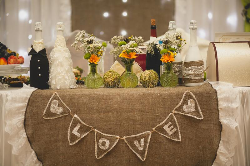 The inscription love in English, on the wedding festive table of the newlyweds. Stylish modern decoration of the table of the. Bride and groom for the Banquet royalty free stock image