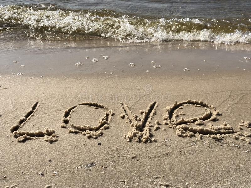 The inscription Love on the sandy shore. Sign drawn on the sand, closeup. royalty free stock photography