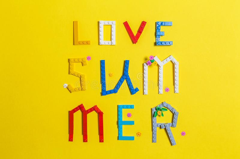 Inscription love summer layed out on a yellow surface. Inscription love summer made from multicolored parts of constructor is layed out on a yellow surface. Top stock images