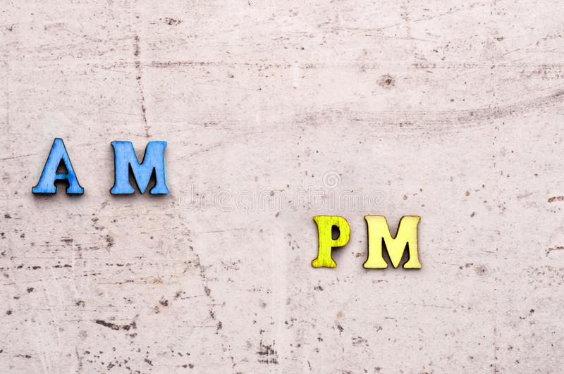 A.m. ante meridiem, in the morning, p.m. post meridiem, in the afternoon abbreviation in wooden letters on a light background stock photography